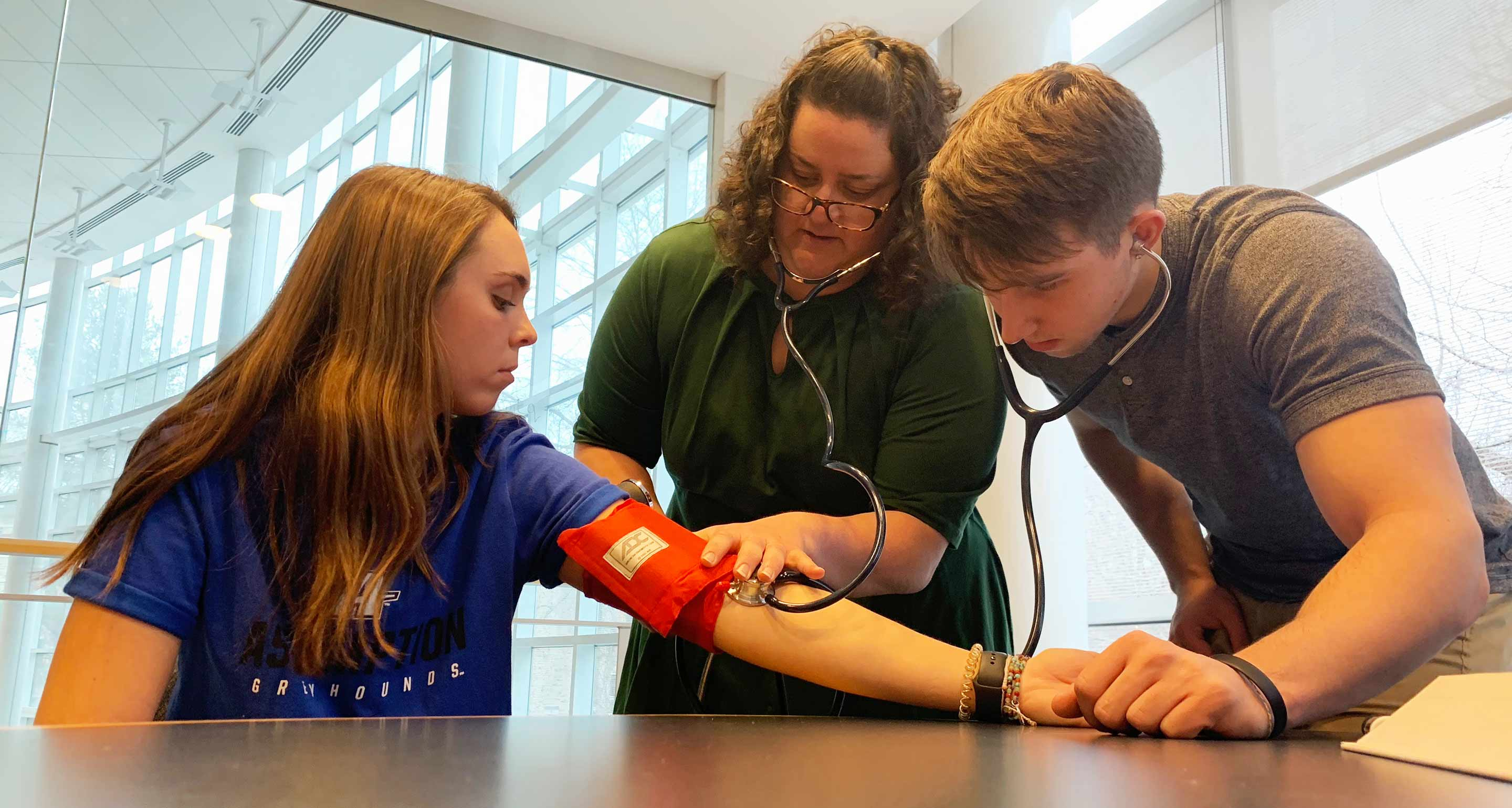 Students learning to use a blood pressure cuff
