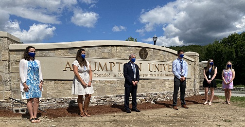Assumption University President Francesco Cesareo poses in front of the new University sign with students